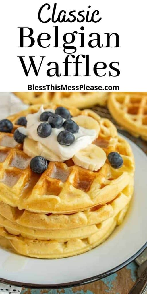"""picture of Beglian waffles stacked on a plate, topped with blueberries, banana slices, and whipped topping with the words """"classic Belgian waffles"""" written at the top"""