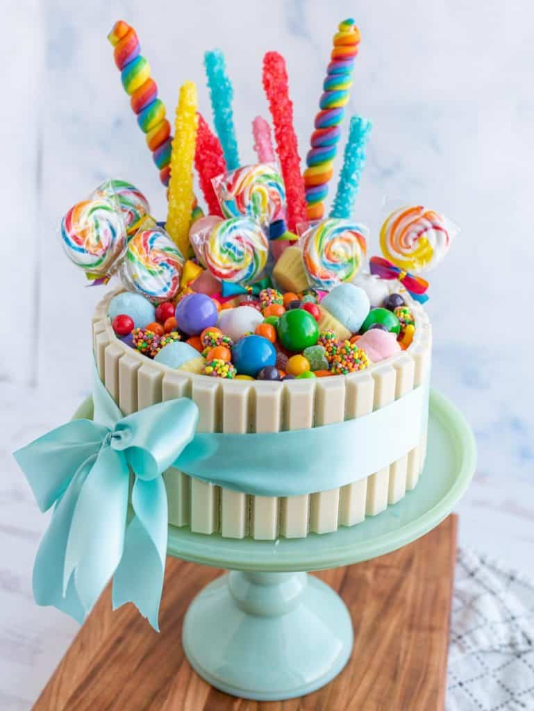 picture of a candy cake on a cake plate, with a bow wrapped around it