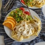 up close picture of a plate of alfredo pasta with salad and orange slices