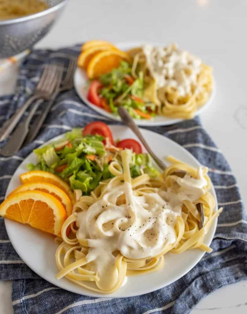 plates of alfredo with salad and orange slices