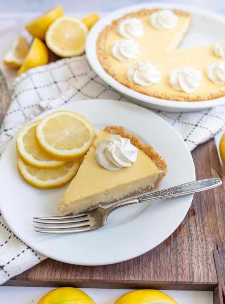 a plate of lemon pie next to the pie