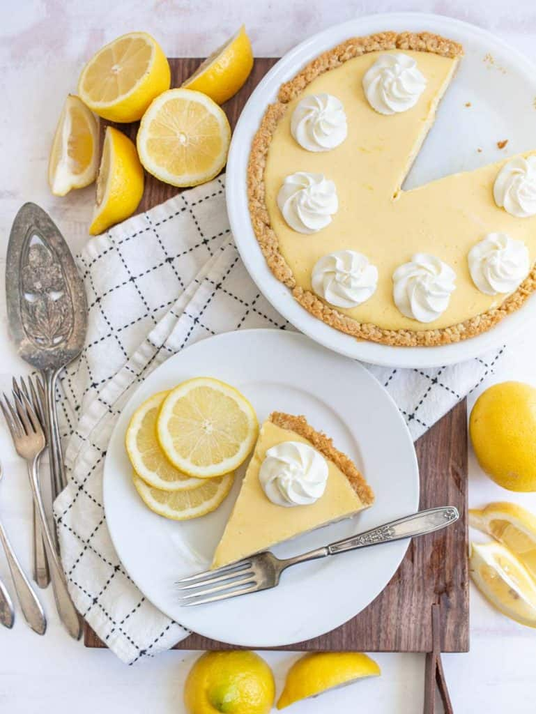 top view of a plate of lemon pie next to the pie