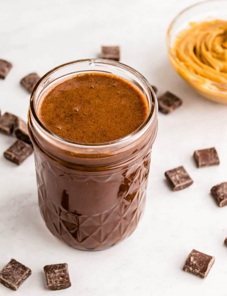top view of a jar of peanut butter hot fudge with a bowl of peanut butter and chocolate chunks surrounding it