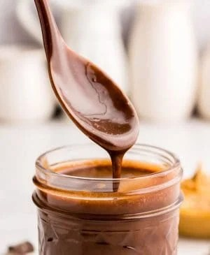close up picture of a spoon covered in peanut butter hot fudge over a jar of peanut butter hot fudge