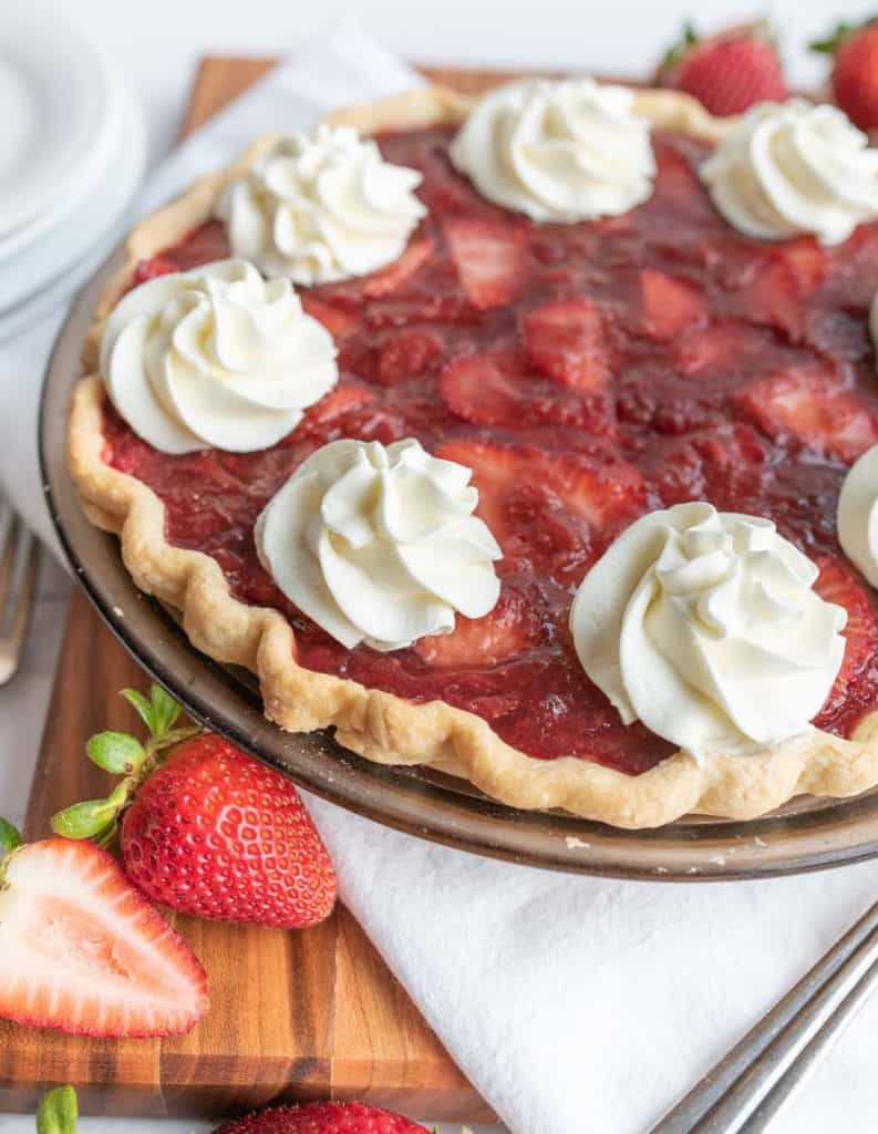 up close picture of a strawberry pie with dollops of whipped cream
