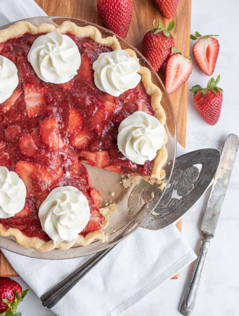 top view of a strawberry pie with dollops of whipped cream on it, with a slice missing