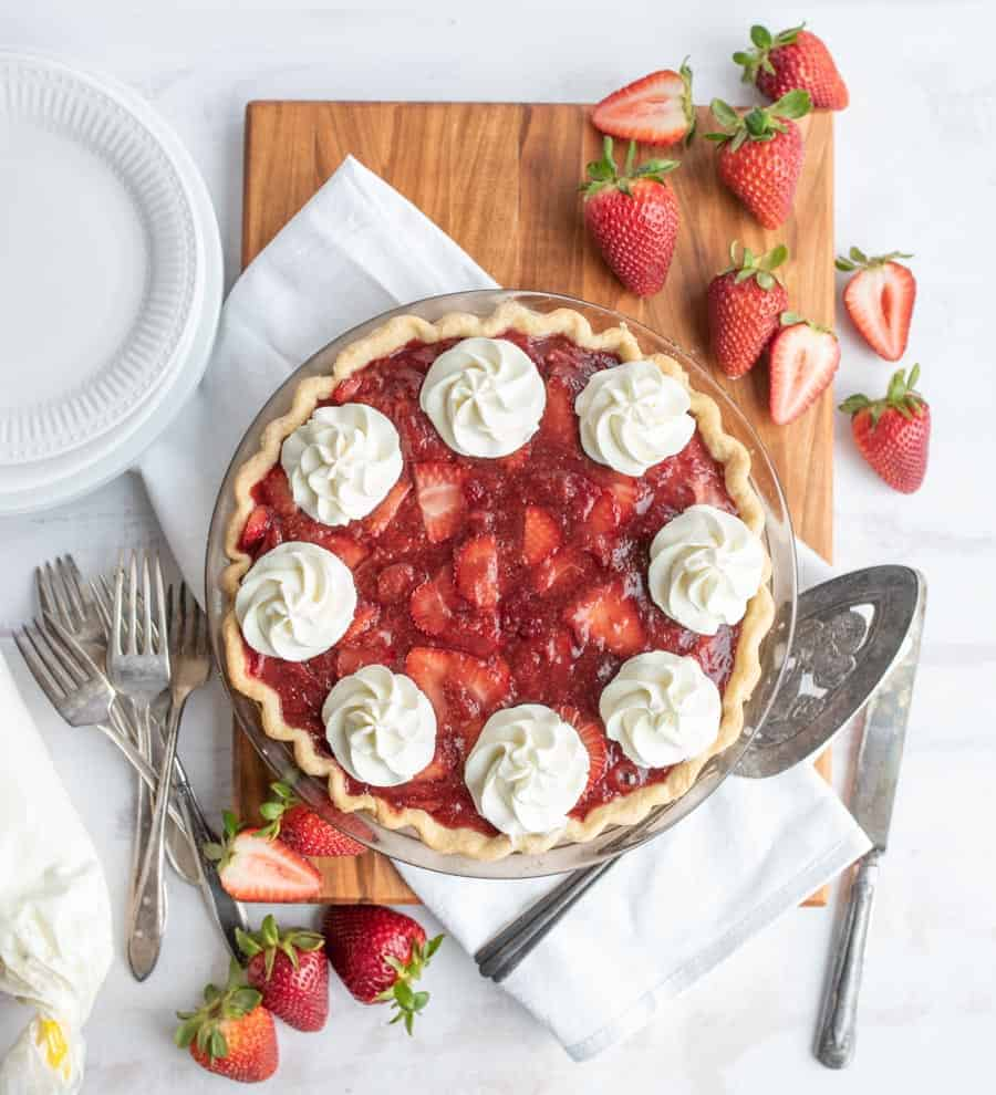 top view of a strawberry pie with strawberries and serving utensils around it