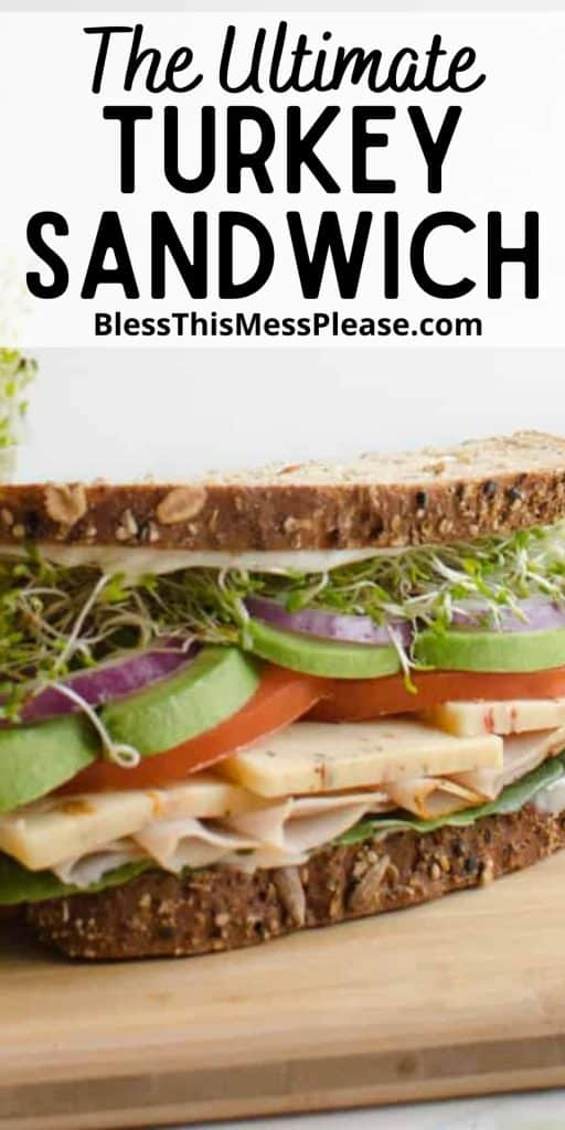 """close up front view of a turkey sandwich with the words """"The Ultimate Turkey Sandwich"""" written at the top"""