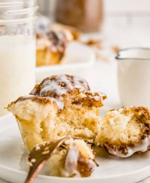 monkey bread muffin cut in half on plate with cup of milk in background
