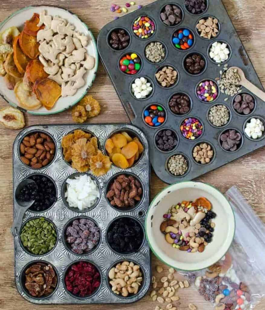 top view of ingredients in a bowl for trail mix next to muffin tins filled with ingredients for trail mix