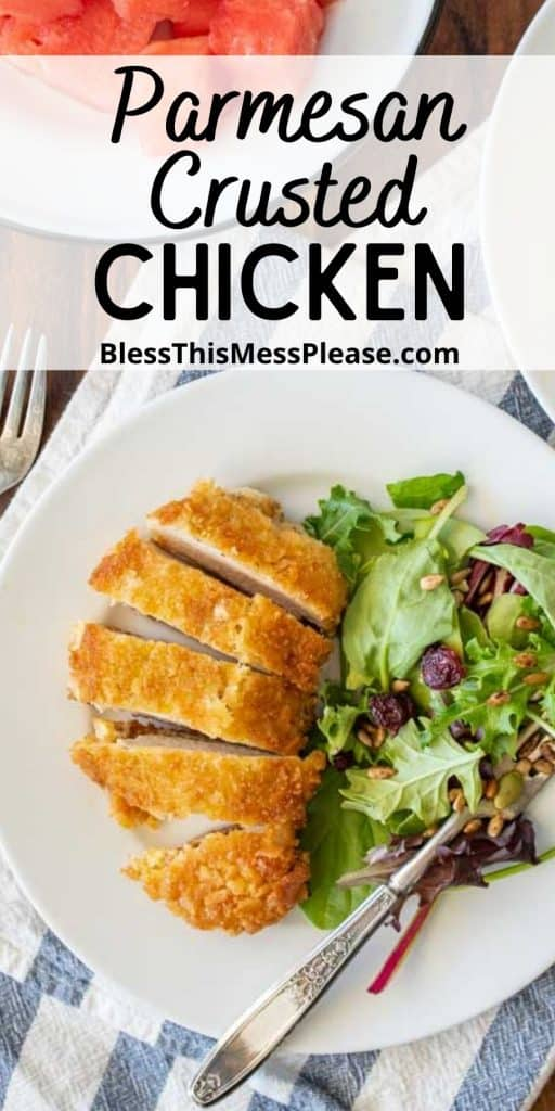 """top view of a plate of parmesan crusted chicken sliced into pieces with a salad on the side and the words """"parmesan crusted chicken"""" written at the top"""