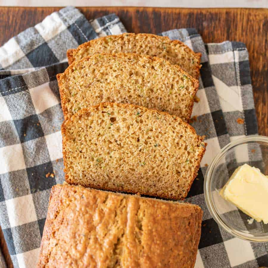 close up top view of slices of banana bread on a towel next to a bowl of butter