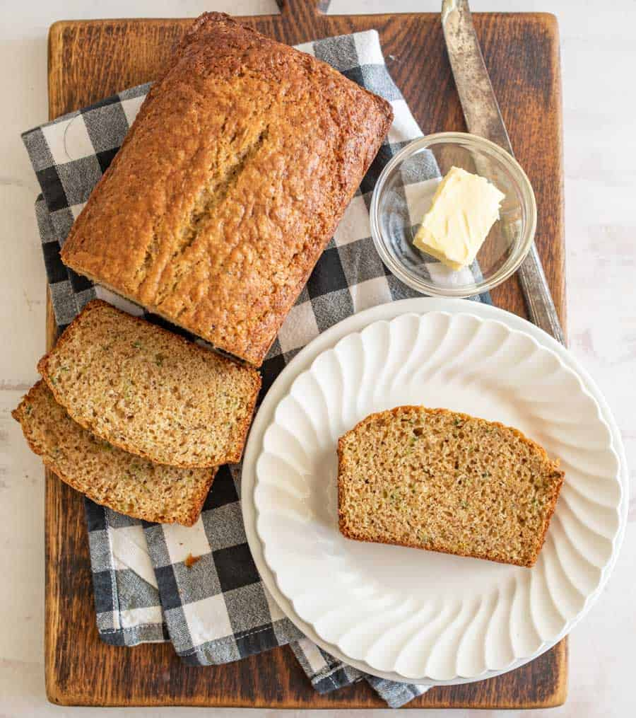top view of a loaf and slice of banana bread next to a slice of bread on a plate and a bowl of butter
