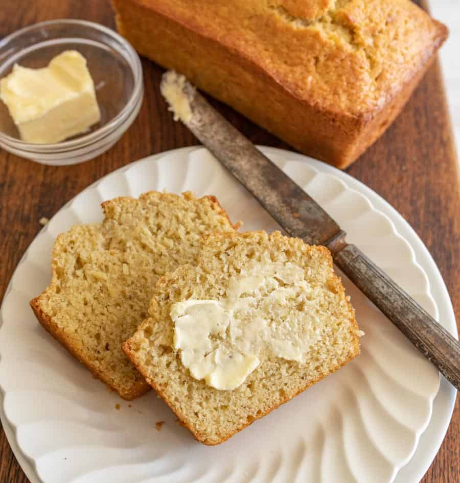 close up of slices of buttered banana bread on a plate with a knife next to them