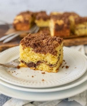 close up picture of a piece of coffee cake on a plate with a fork next to it