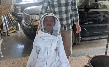 child in an adult bee suit
