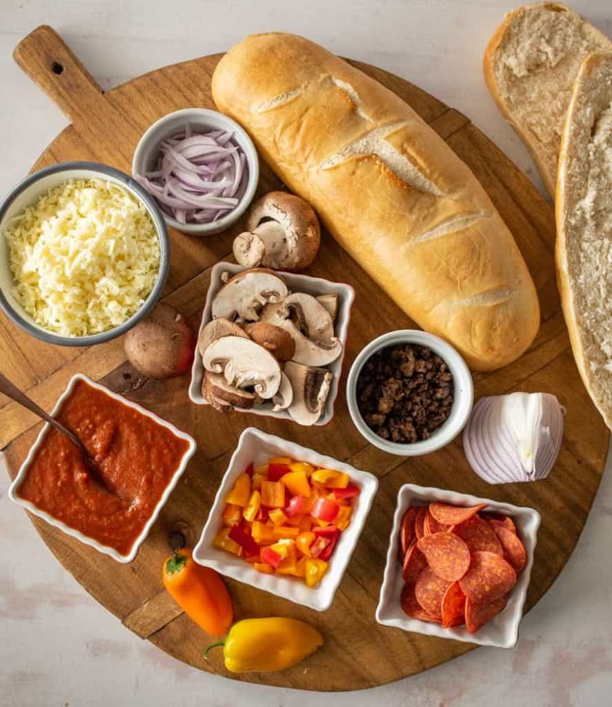 ingredients for French bread pizza sorted out on a cutting board