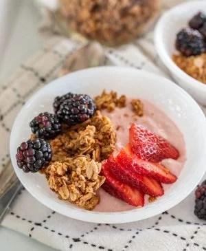 bowls of yogurt with granola and berries on it