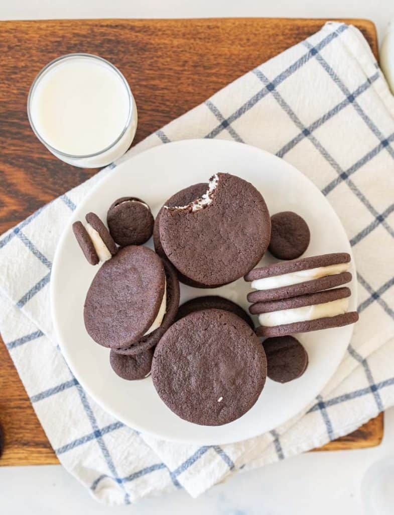 top view of a plate of homemade oreos with a glass of milk next to it