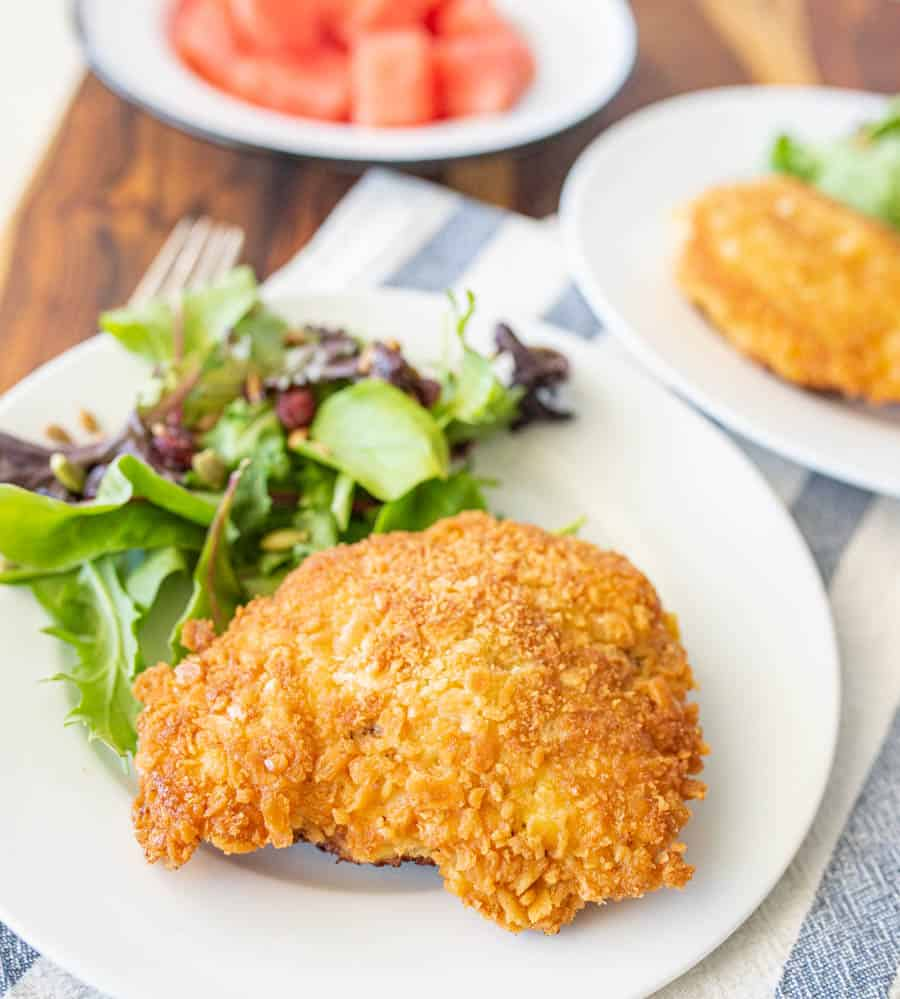 parmesan crusted chicken and salad on a white plate