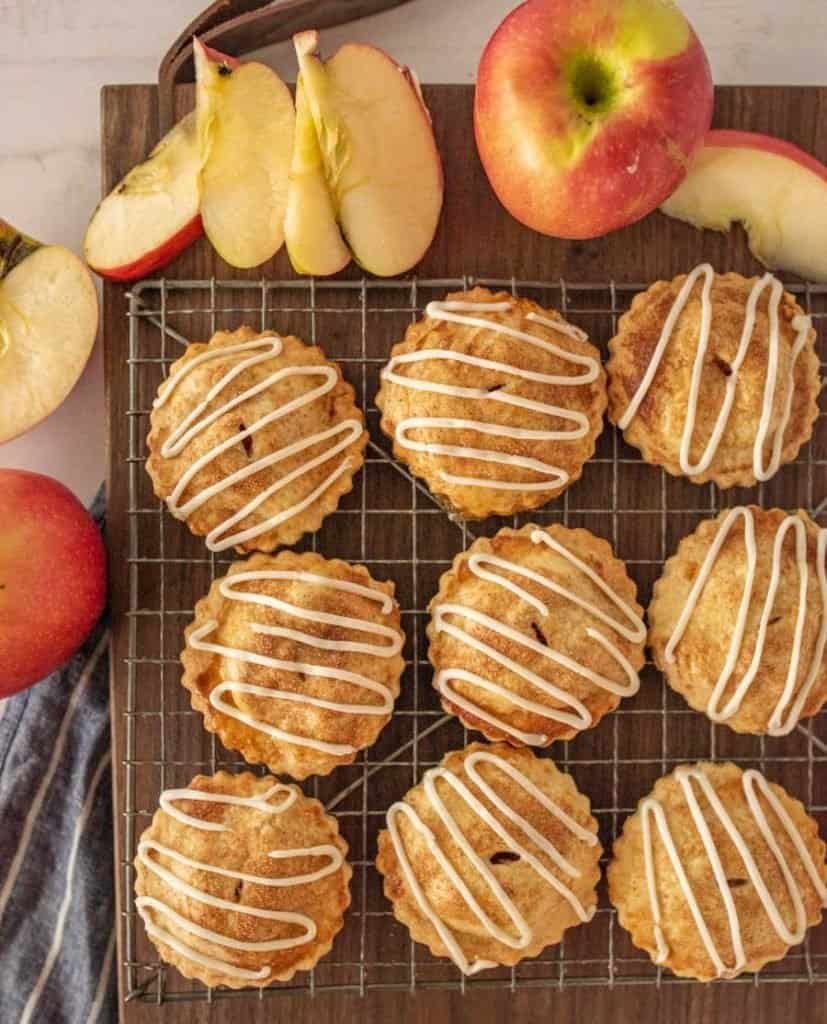 top view of apple hand pies on a cooling rack with apples on the side