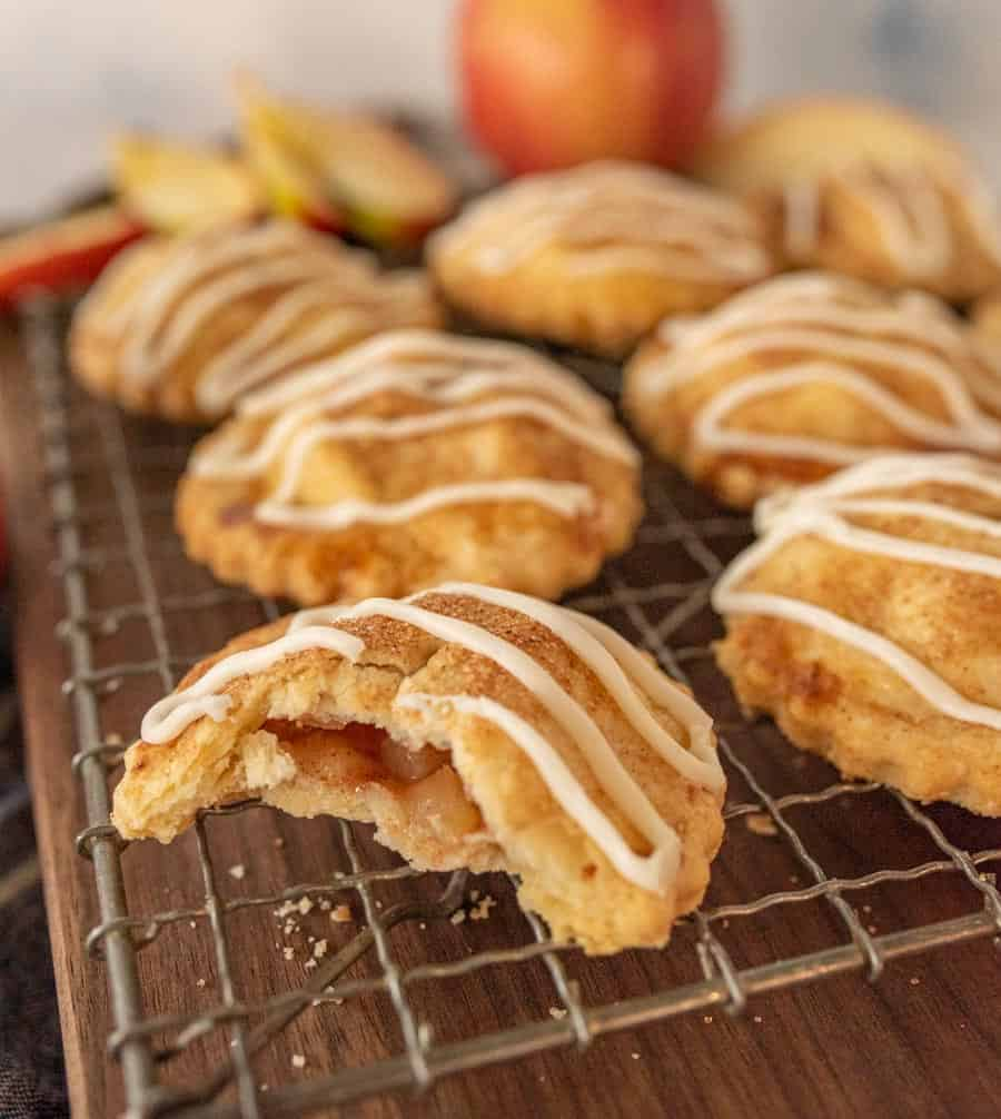 close up of an apple hand pie with a bite taken out of it on a cooling rack