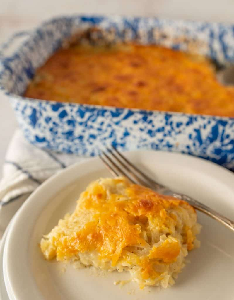 cheesy potato casserole on a plate with a fork and the baking dish in the back