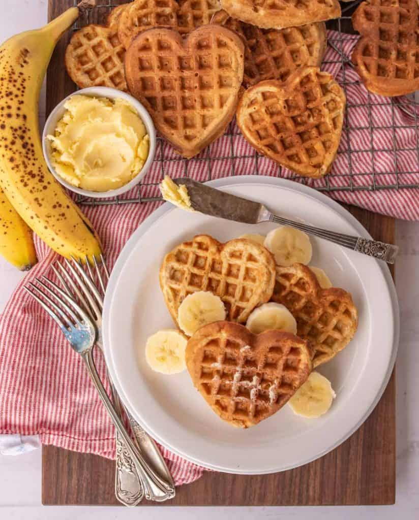 top view of heart shaped waffles and slices of bananas on a plate with utensils, bananas, bowl of butter, and other heart shaped waffles on a cooling rack