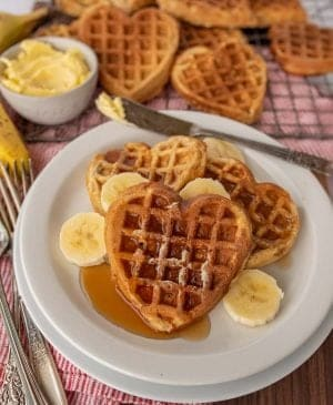 heart shaped waffles on a plate with syrup and banana slices and waffles in the background