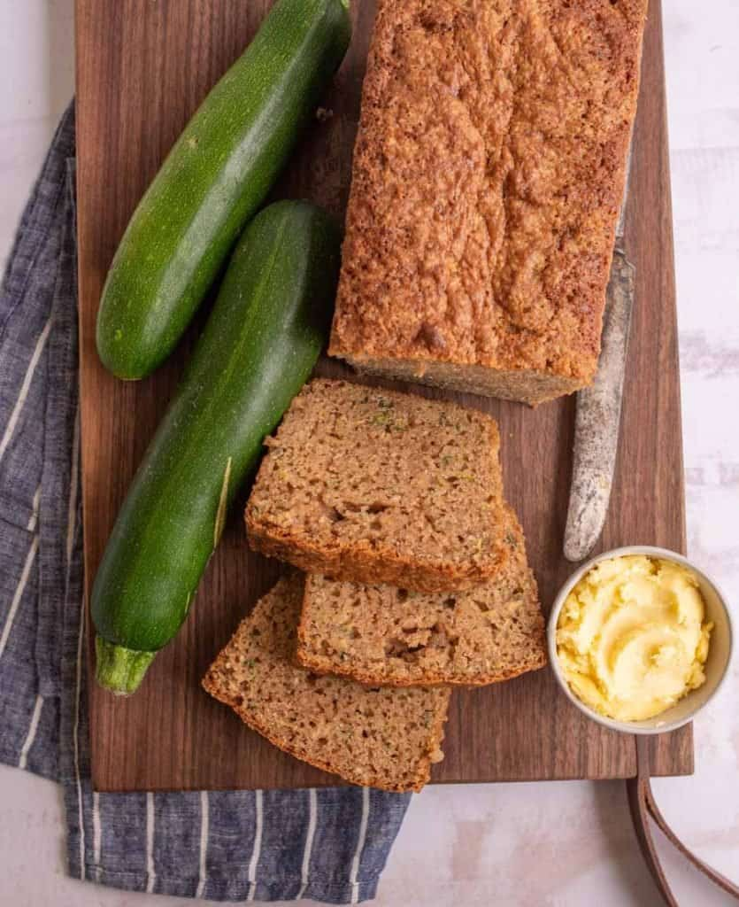 top view of a loaf of zucchini bread with some slices cut out of it next to zucchinis and a bowl of butter