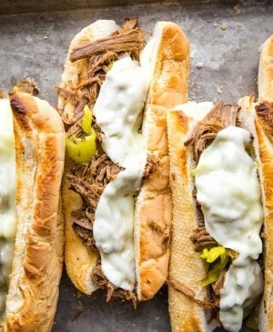 top view of a pan of Italian beef sandwiches with melted cheese on top