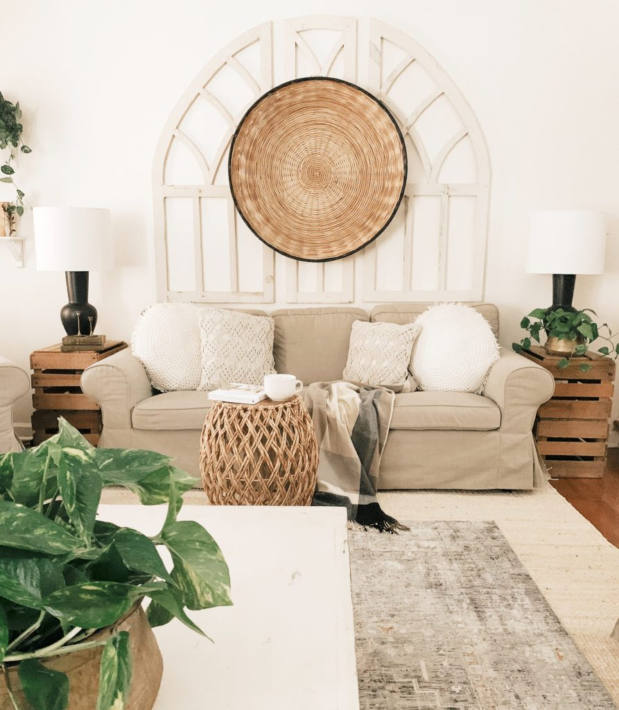 arched windows behind sofa with large round basket in the center