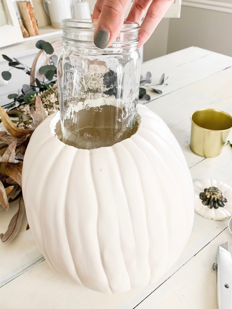 putting mason jar in hole in the top of the pumpkin
