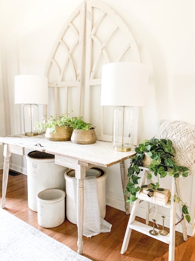entryway table with arched windows and lamps.
