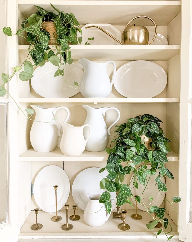 farmhouse hutch with white dishes and greenery