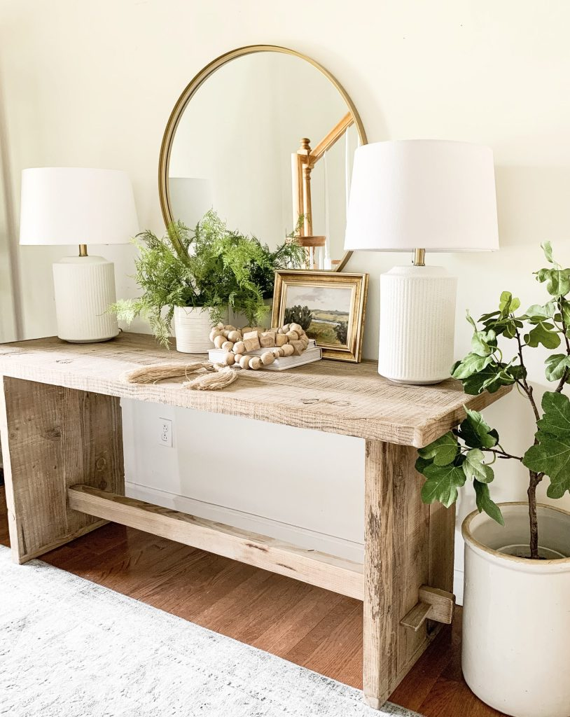 wood entryway table with brass round mirror