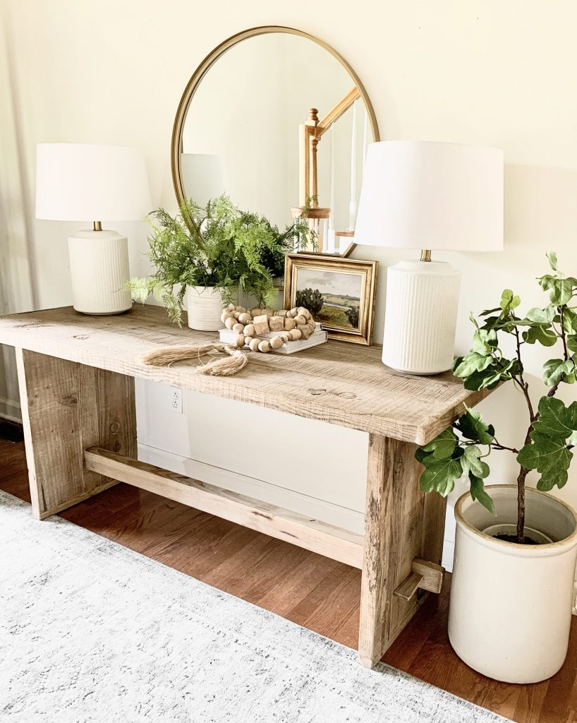 entryway table with decor pieces and round mirror