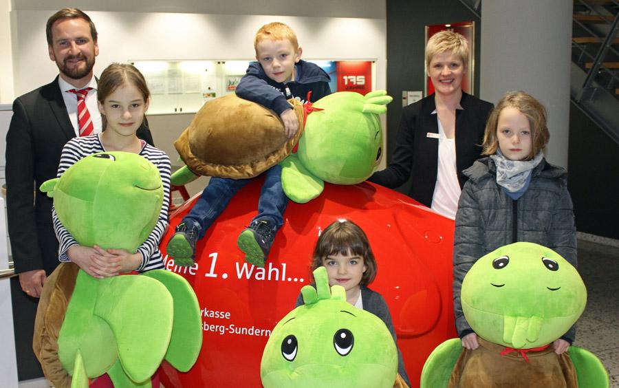 Vier Weltspartag-Gewinner freuen sich über Eddi, die Riesenschildkröte