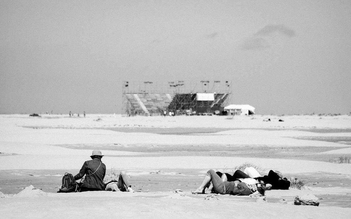 Oerolgangers op het strand met een tribune op de achtergrond.