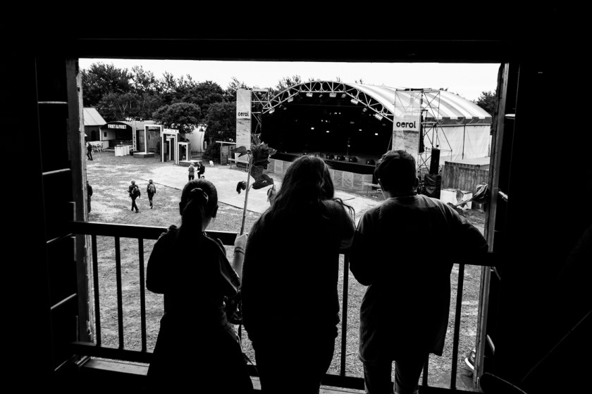 Drie kinderen kijken naar het festivalterrein van boven.