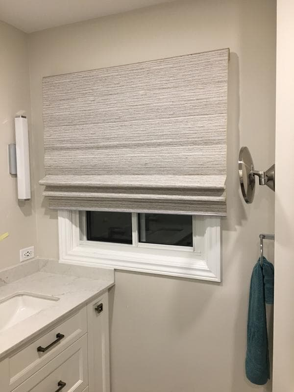 bathroom window covered with roman shade in grey woven fabric