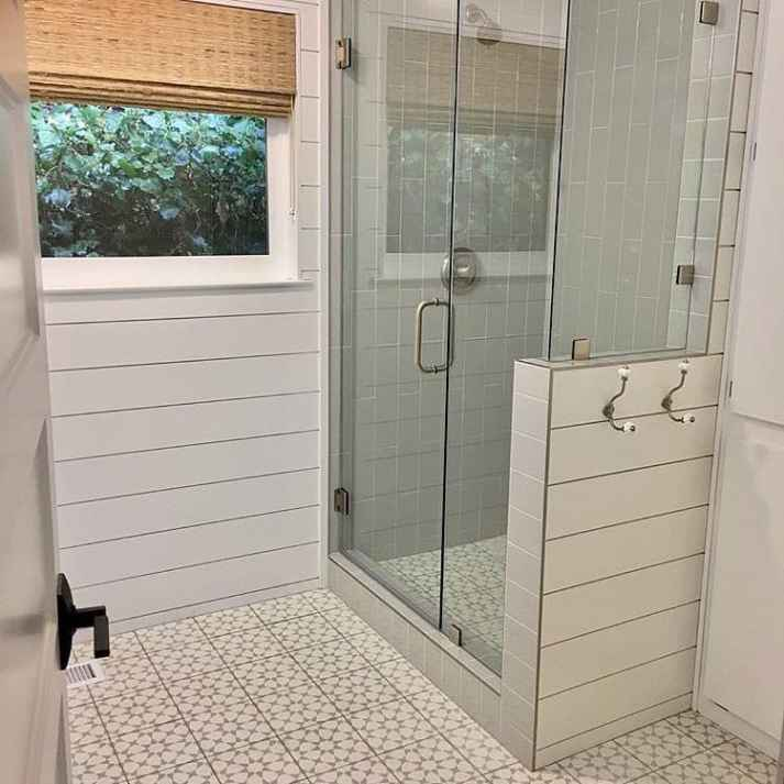 bathroom with patterned tile floor, shiplap walls and woven wood shade over window