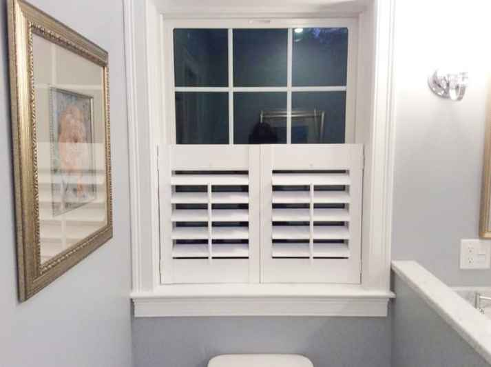 bathroom window covered with half cafe shutters