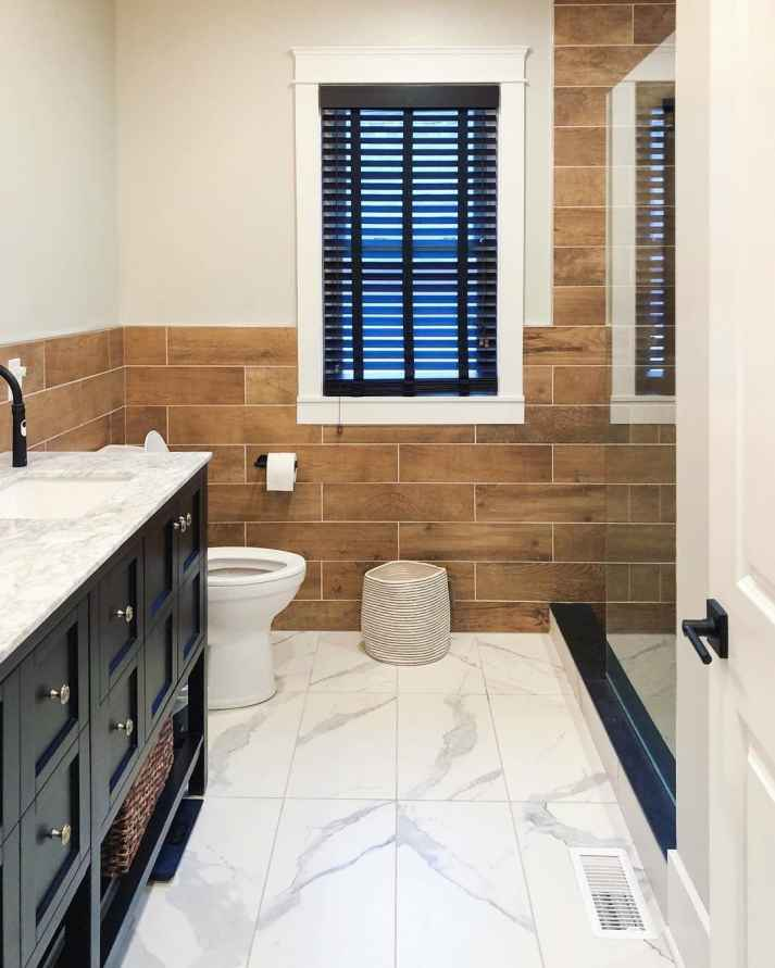 bathroom with marble tile floors, wood tile walls and window covered with black blinds with cloth tapes