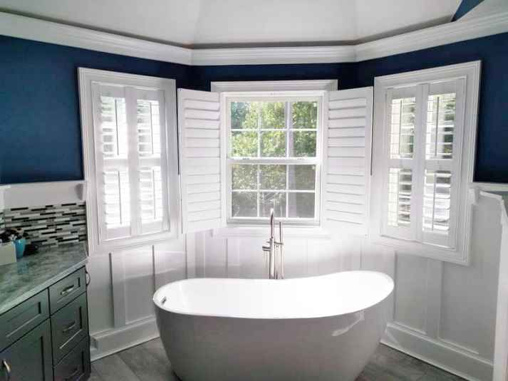 bathroom with bay window behind bathtub, covered with plantation shutters