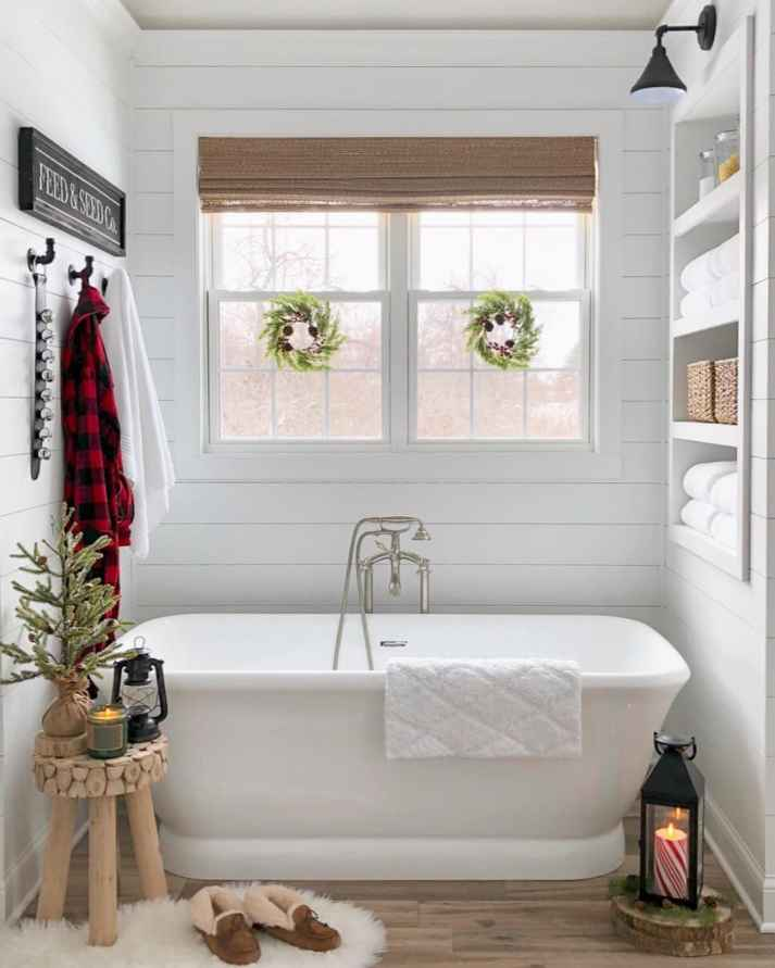 woven wood shades in bathroom window with freestanding tub in niche with shelves