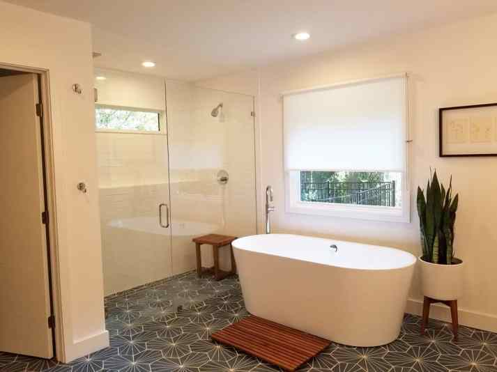midcentury bathroom with modern freestanding bathtub, glass shower enclosure, blue printed tile and white sheer roller shade over window