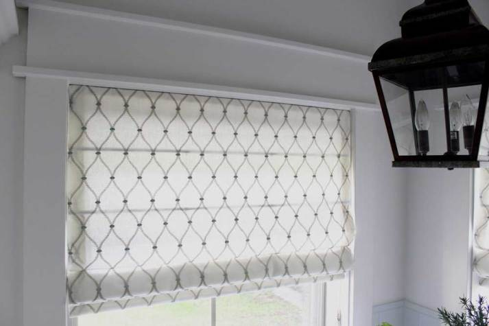 Close-up of Blinds.com roman shades installed in window