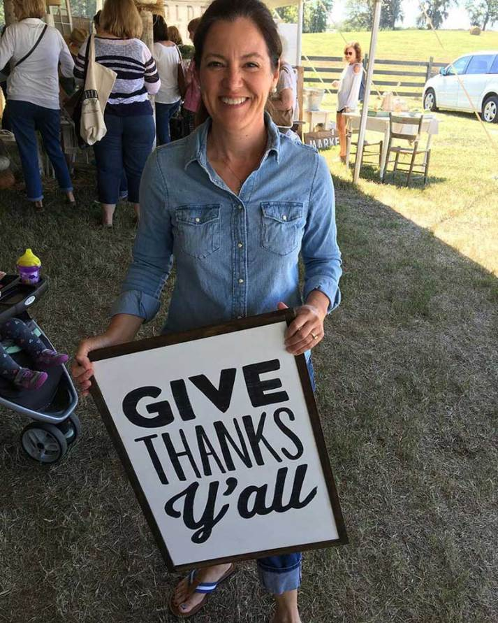 "Susie Harris holding ""Give thanks y'all"" sign"
