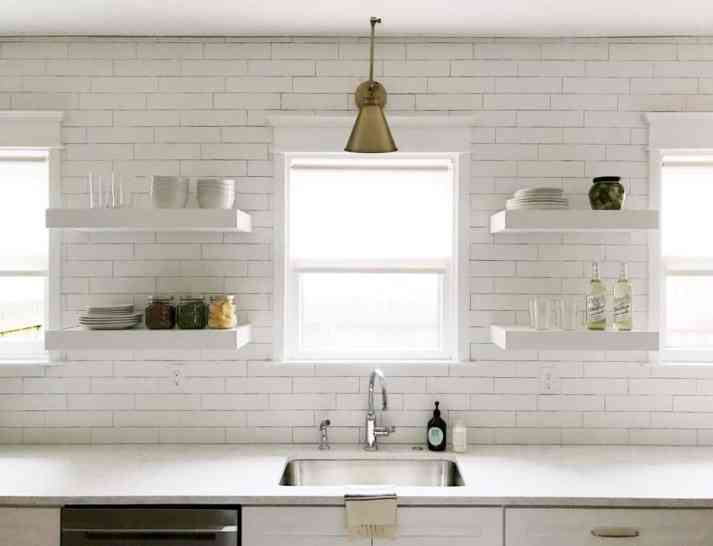 kitchen with white subway tile white open shelving and triple windows with white roller shades and brass swing arm sconce above window